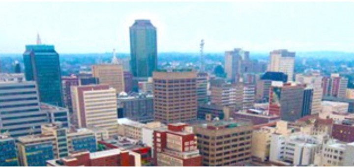 """Over a lifetime, the Harare skyline has changed beyond recognition. With notable exceptions – the High Court, the foreign ministry, the Munhumatapa building ( time on the clock tower has long been stopped at twenty past three) - most of the squat colonial buildings are gone, giving way to gleaming towers of steel and glass. An old man on his first trip from deep in the rural areas marvelled at the new buildings and remarked that us the townspeople appeared to be obsessed with glass. """"You even cover your eyes with it,'' he said to a bespectacled me. He wasn't impressed at all by the Karigamombe Centre or the faded gold façade of the Rainbow Towers – """"Golden Delicious"""" as it was known to taxi drivers before the elements of sun and storm took their toll on the then Sheraton. Nor was he impressed by the imposing edifice of the central bank. On the bus on the main road from the west he could see the Reserve Bank from some 20 kilometers away. It is designed to be seen from all the city's main approach roads. He didn't know until I told him that the bank's octagonal design is symbolic of an upended maize cob - maize being the once abundant staple food and the cob-like skyscraper represents the Horn of Plenty, the nation's cornucopia. Inside, it has marble trimmings and suites and boardrooms to match the best in Frankfurt or London. Alas, as the economy took strain in recent times, the Horn of Plenty emptied soon emptied. A few blocks away, across my home town, is Eastgate, a fine shopping mall and office complex behind Meikles hotel that has rows of rooftop chimneys. When the building is lit after dusk it looks like an old steamship ploughing into the night. It was Zimbabwe's first really """"green"""" construction project, based on nature's self-ventilating anthill. Its designers insisted it saved 70 percent of the energy costs the central bank building would gobble up. Walking on chill winter mornings in the multiple green belts and vleis of Harare, I have often watched conden"""